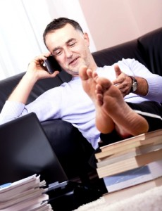 Businessman working with his feet up and on the phone