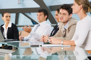 people sitting around conference table looking happy