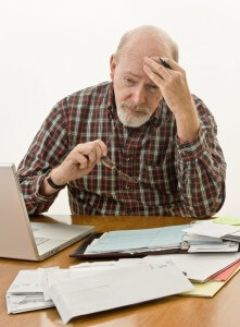 man looking stressed with paperwork
