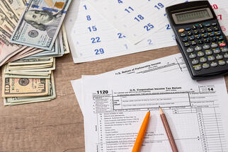 tax forms with money and calculator