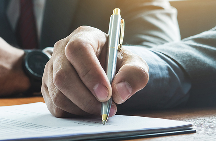 Man holding a pen while and signing a document