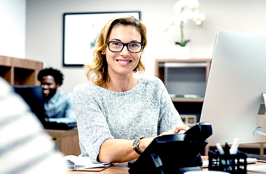 Woman smiling as she works at her desk