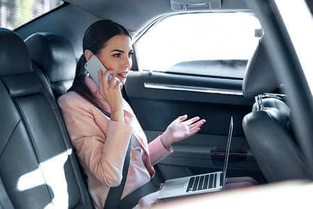 Woman in the car with her laptop on her lap and talking on the phone