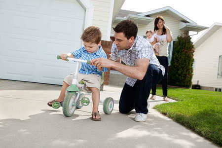 Father teaching son to ride tricycle