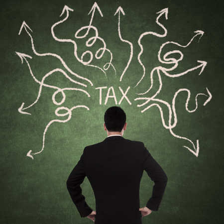 A man standing in front of a wall with the word Tax written on it and arrows pointing in different directions