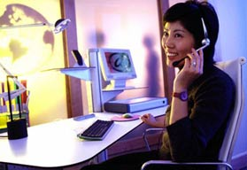 woman with headset smiling at desk