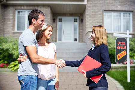 Man and woman shaking hands with their real estate agent. The house behind them has a SOLD sign.